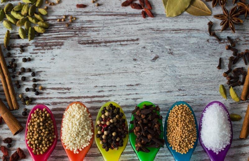 Underbara kryddor i de färgrika skedarna Placer av olika kryddaingredienser royaltyfria bilder