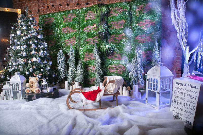 Underbart julläge med efterföljd av snö, istappar, dekorerad julgran, barns pulkor, granfilialer med royaltyfri bild