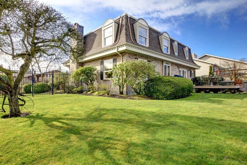 Underbart klassiskt hus för stenfasadbeklädnad med trädgårdblomsterrabatten, tr royaltyfri fotografi