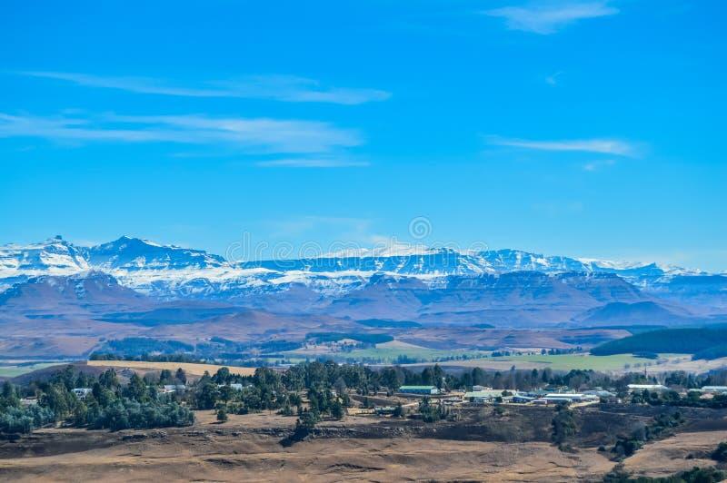 Underberg风景,有被雪复盖的德肯斯伯格山和绿色风景的一个小乡下村庄 免版税库存图片