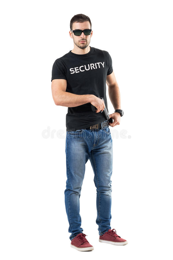 Undercover police man taking handgun from belt looking at camera. stock photos