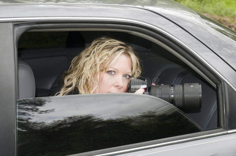 Undercover woman spying camera stock photography