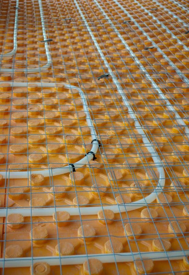 Underfloor heating. Orange posed Underfloor heating tube in a construction site stock images