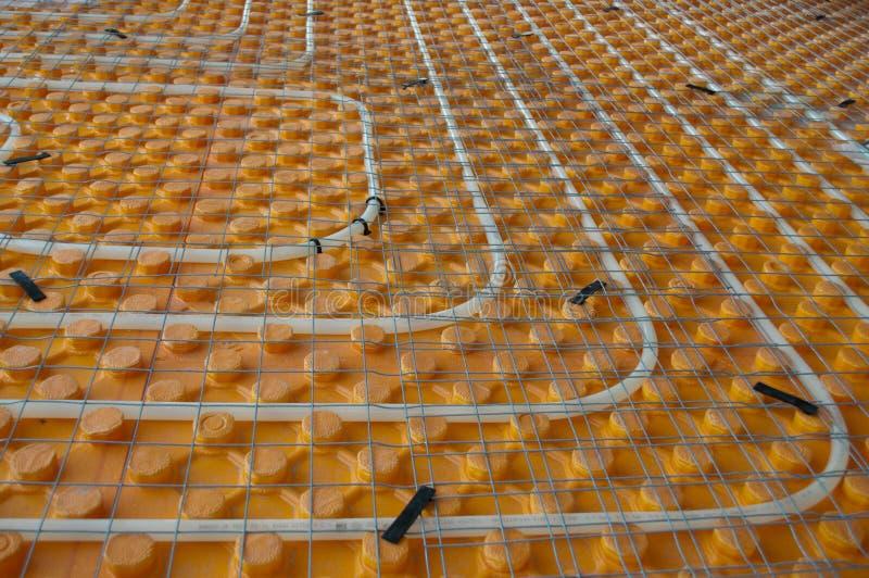 Underfloor heating. Orange posed Underfloor heating tube in a construction site royalty free stock photography