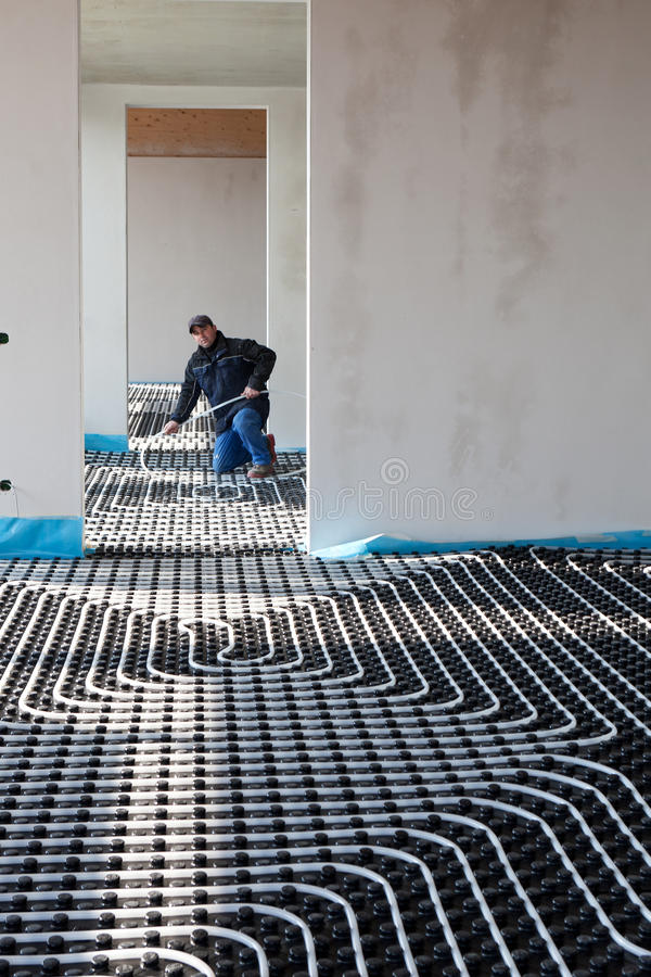 Underfloor heating and cooling. Man work on building site royalty free stock images