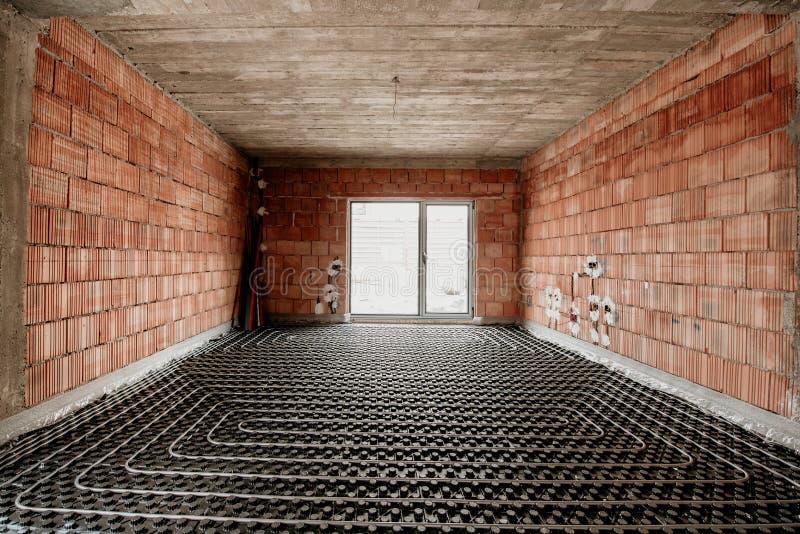 Underfloor uppvärmning i konstruktion av det nya bostads- huset, konstruktionsdetaljer, rörmokeri royaltyfria foton