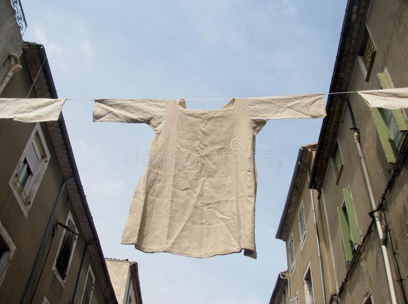 Undergarment shirt hanging on a clothesline. Between the buildings royalty free stock photography