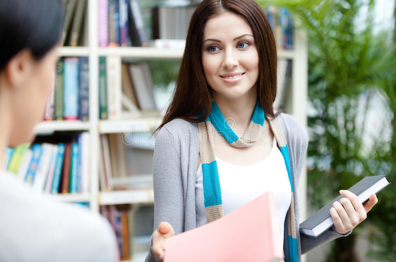 Download Undergraduate Offers A Book To Her Friend Stock Photo - Image: 30457760