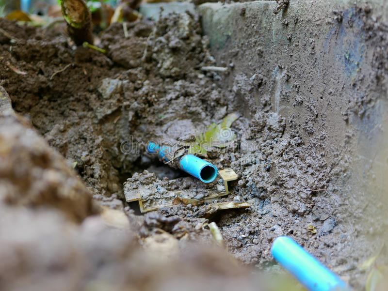 Underground broken / leaked / cracked PVC, polyvinyl chloride, water pipe is partly cut off, getting ready to be fixed. Selective focus of underground broken / royalty free stock images