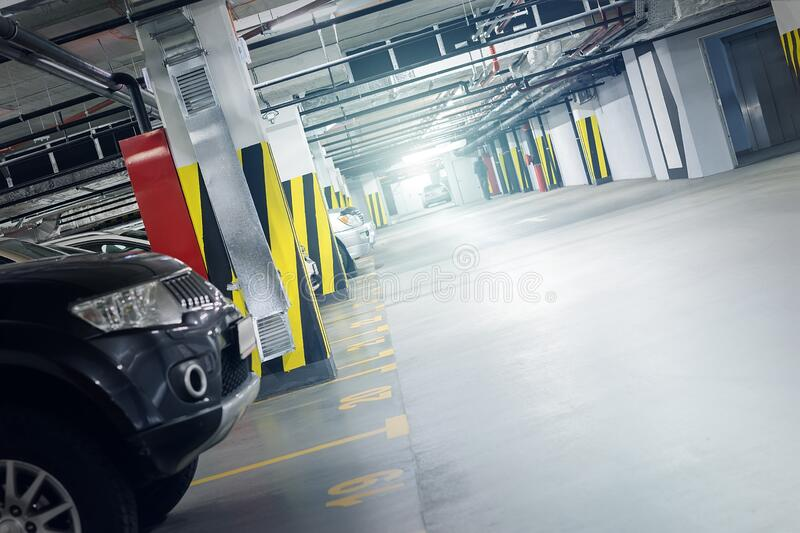 Underground car parking interior in basememnt floor shopping mall, office business center or residential apartment building. Covered vehicle garage indoor stock photography