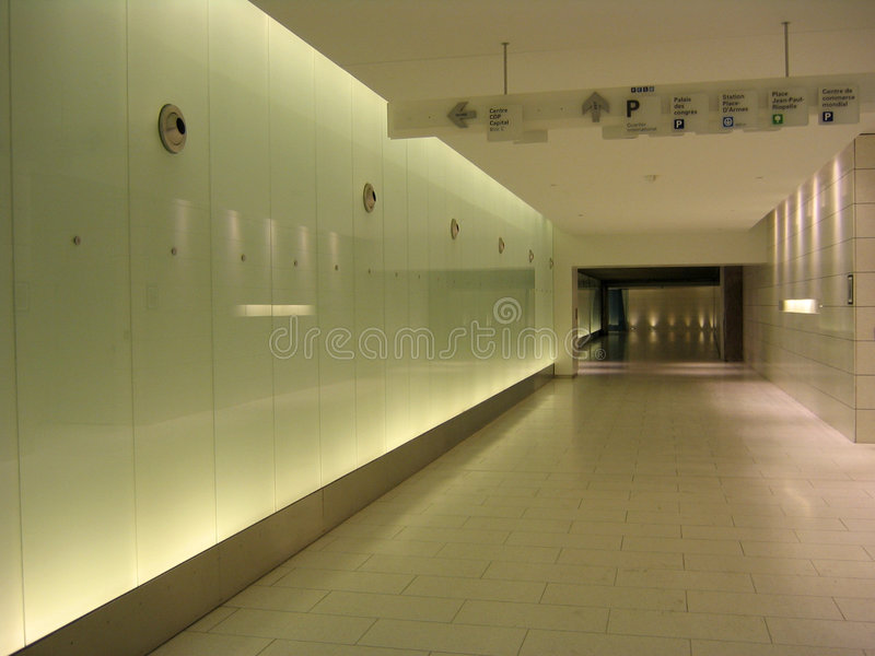Underground corridor, signs and back-lighted walls stock images