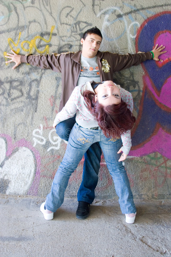 Underground couple. Young boy and girl against a graffiti wall stock images