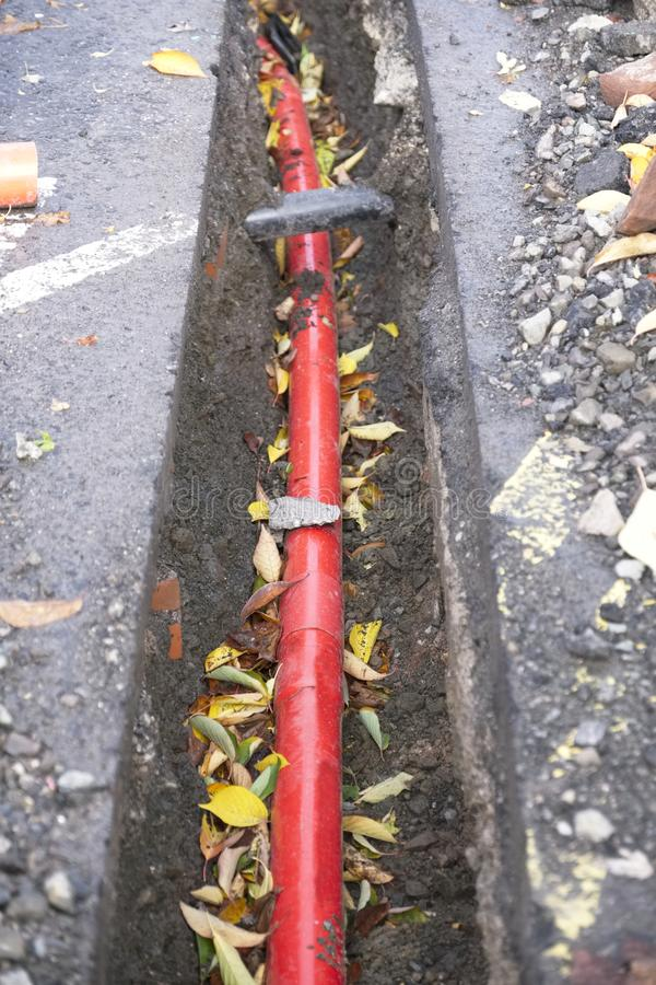 Underground electrical red cable duct in trench at construction building site stock image