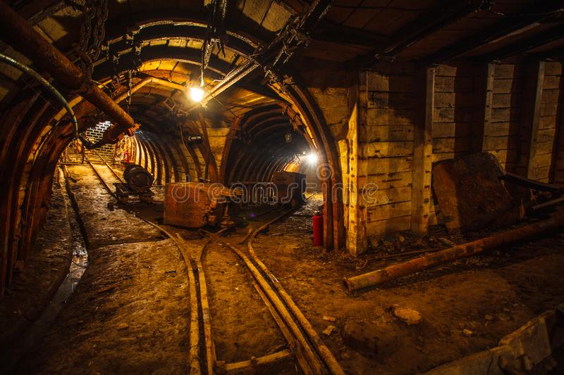 Underground mining tunnel with rails. Copy space. Work in an underground coal mine royalty free stock image