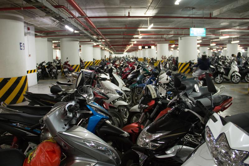 Underground motorcycle parking. Crowded lines of motorbikes syaying one by one. Vietnamese traffic and infrastructure. Underground motorcycle parking in stock images