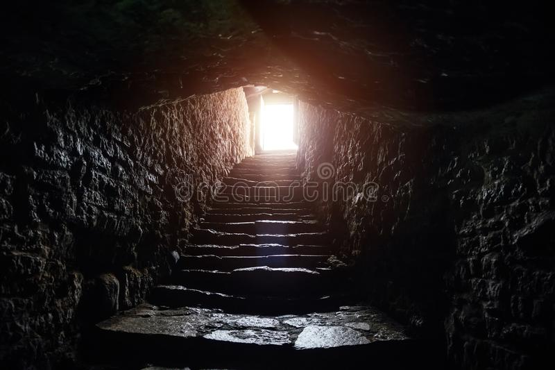 Underground passage under old medieval fortress. Old stone stairs to exit of tunnel royalty free stock image