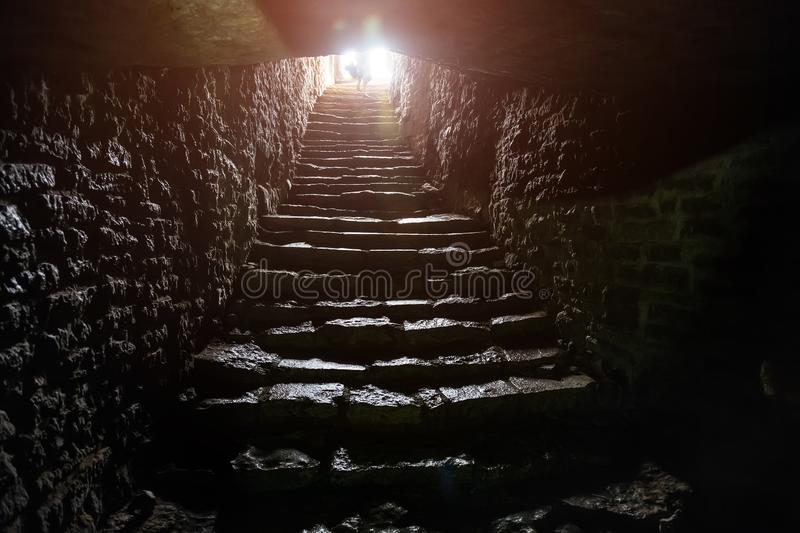 Underground passage under old medieval fortress. Old stone stairs to exit of tunnel stock photos