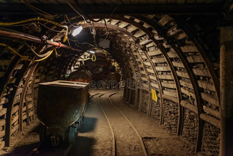 Underground train in black coal mine tunnel stock image