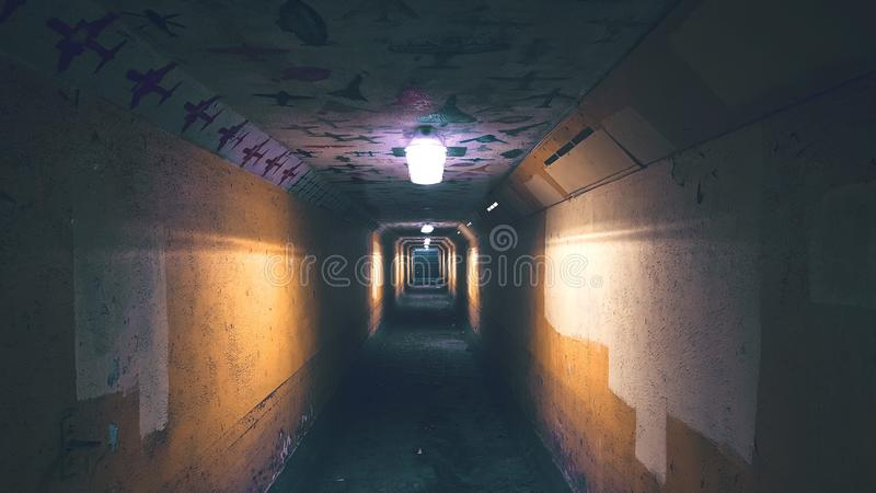 Underground tunnel with brown walls and lights stock photography