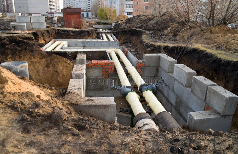 Underground utilities. Laying of communications pipes to homes on the land royalty free stock photos