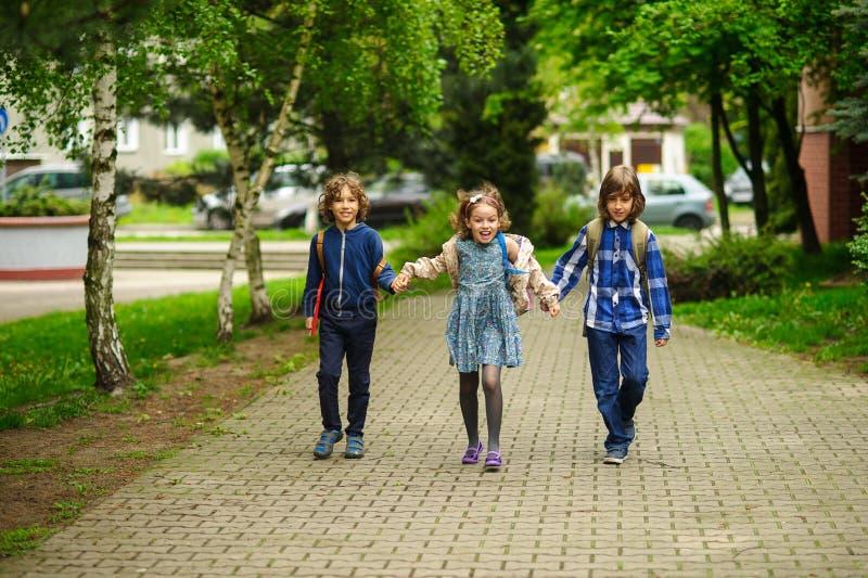 Underhållande små skolastudenter går till skolan som har sammanfogat händer arkivfoton