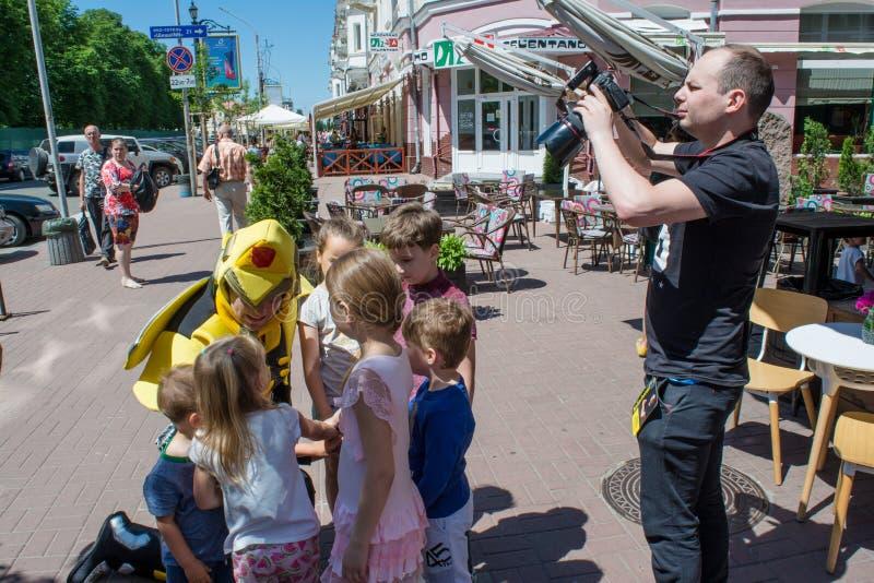 Underhållare som spelar med lyckliga ungar under barnskyddsdag, medan fotografen tar foto royaltyfria foton