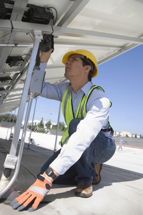 Underhållsarbetare som installerar sol- Photovoltaic paneler royaltyfri bild