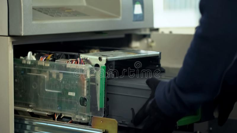 Underhållsarbetaren som sätter in fall med kassa i ATM, bemyndigade tillträde, service royaltyfri foto