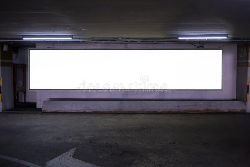 Underjordisk inre för parkeringsgarage med den tomma affischtavlan Töm utrymmeparkeringshusinre på eftermiddagen Inomhus parkerin royaltyfri fotografi