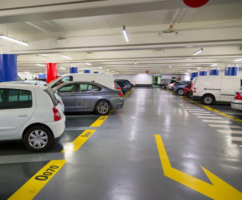 Underjordisk parkeringsplats med bilar arkivfoton