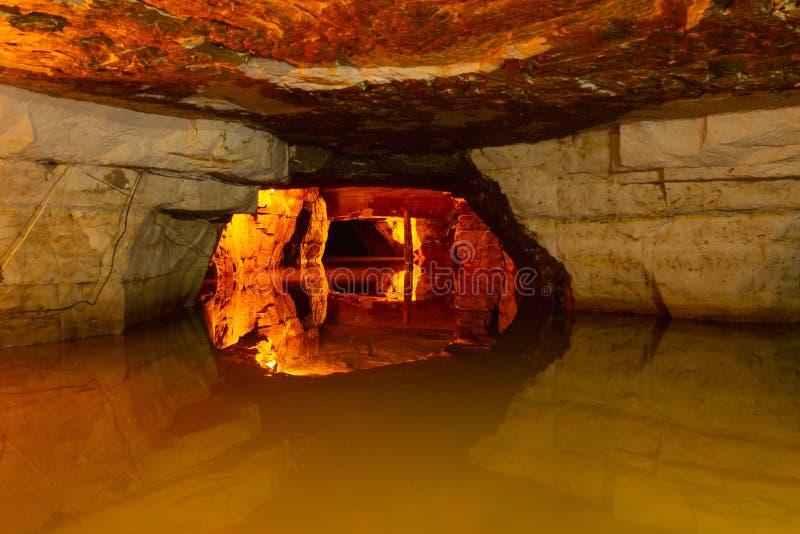 Underjordisk sjö i en stengrotta exponerad av varmt ljust landskap royaltyfri bild