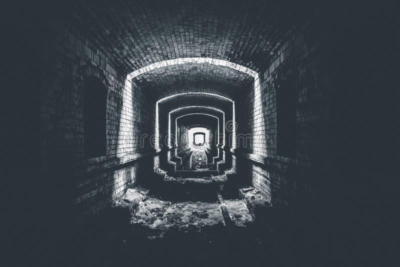 Underjordisk tunnel för förstörd tegelsten eller korridor och ljus i slutet, väg att hoppas begreppet, svartvitt foto royaltyfri bild
