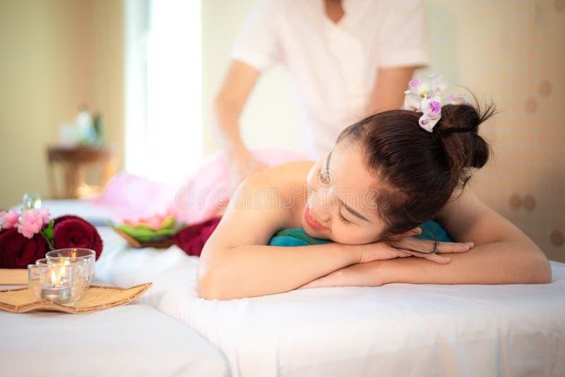 Underminera massagen Massören som gör massage med behandlingsocker, skurar på asiatisk kvinnakropp i den thailändska brunnsortliv royaltyfri bild