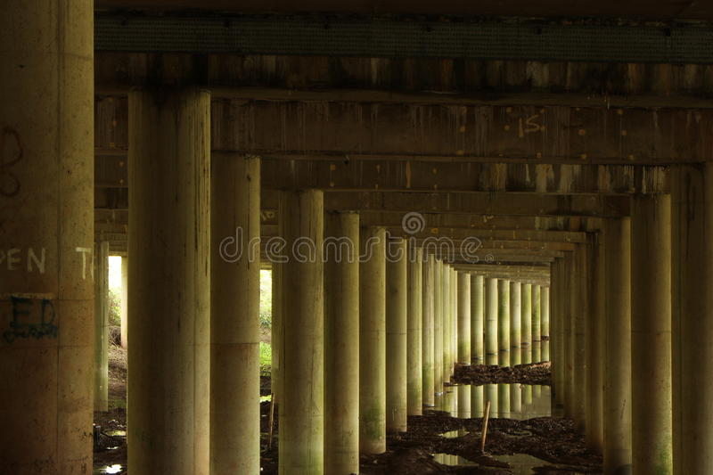 Underneath the bridge columns. A row of concrete columns supporting a road bridge sunk into mud and puddles in the rainsoaked ground stock image