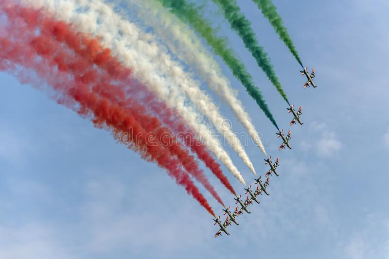 Underneath of PAN military team in steep turn releasing tricolor smokes at airshow, Linate, Italy. LINATE MILAN, ITALY October 12 2019  - underneath of  Italian royalty free stock photo
