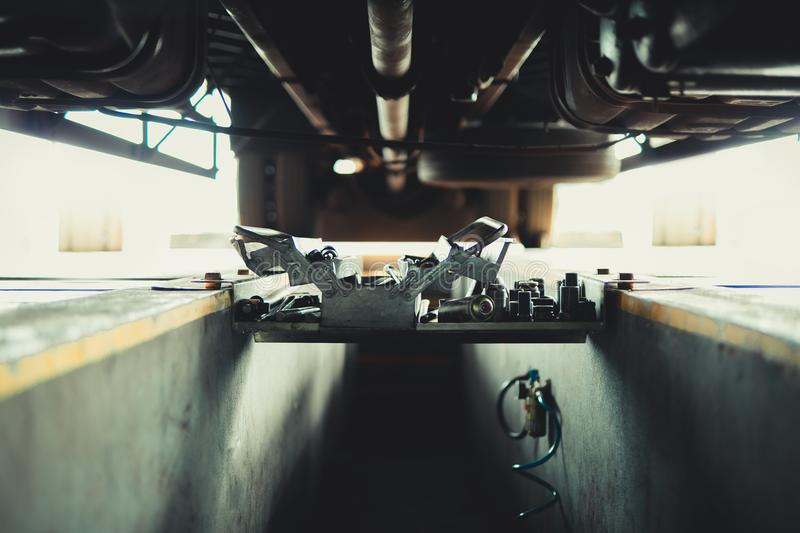 Underneath of a truck. As seen from vehicle inspection trench with the tools for the mechanic fix the truck royalty free stock images
