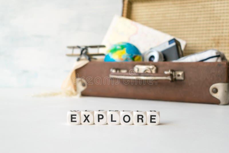 Undersök: Äventyra loppferier Lopp affärsföretag, semesterbegrepp Ordet UNDERSÖKER och bryner den retro resväskan med handelsresa arkivbild