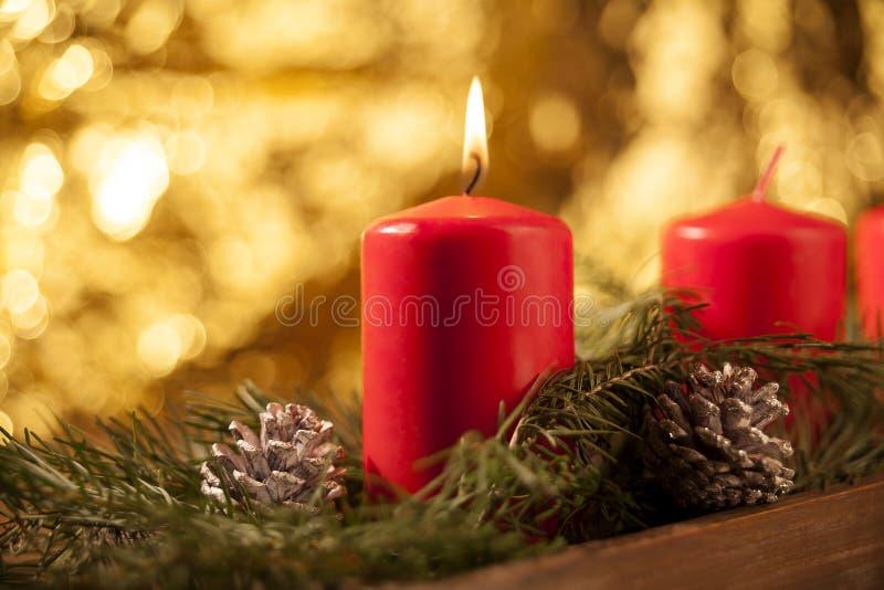 Undersöka först bränningen på en röd Adventkrans arkivbild