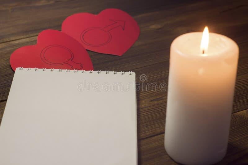 Undersöka kvarter och stearinljuset för två hjärtor på en träbakgrundsanteckningsbok royaltyfria foton