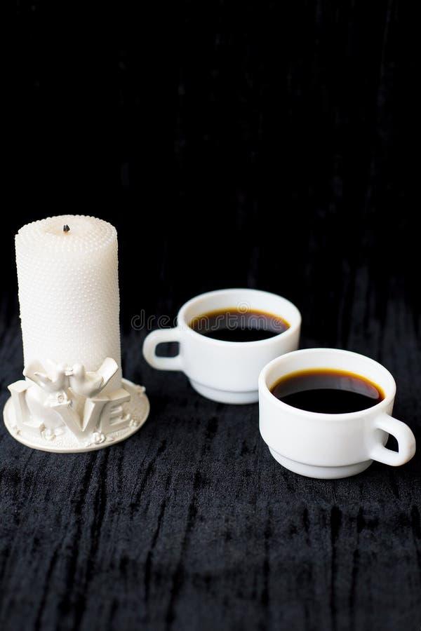 Undersöka och två koppar kaffe på en svart bakgrund arkivfoton