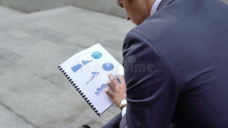 Undersökande affärsgrafer för eftertänksam finansiell konsulent, företag som går bankrutt royaltyfria bilder