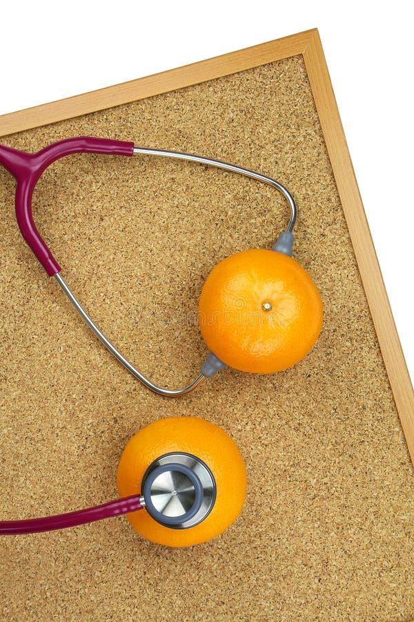 Undersökande apelsin för stetoskop på ett korkbräde Medicinsk utrustning fotografering för bildbyråer