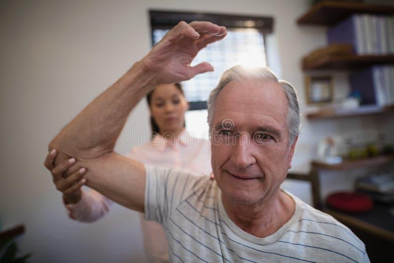 Undersökande armbåge för kvinnlig doktor av den manliga höga patienten royaltyfri foto