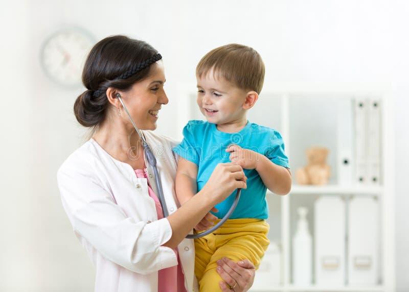 Undersökande barnpojke för kvinnlig doktor med stetoskopet arkivfoto