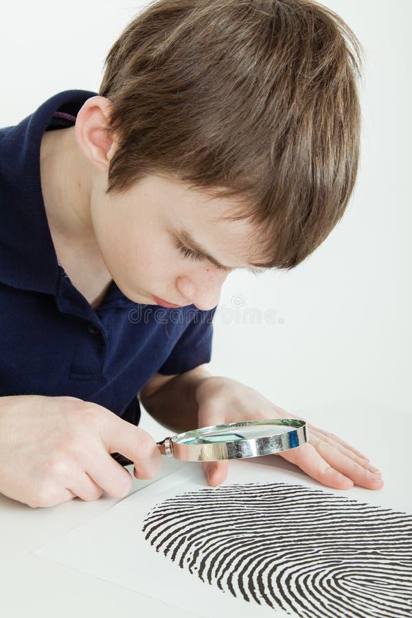 Undersökande fingeravtryck för pojke med förstoringsglaset royaltyfria bilder