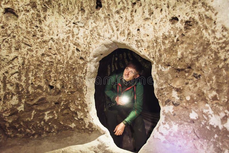 Undersökande grottor för man i Derinkuyu tunnelbanastad royaltyfri foto
