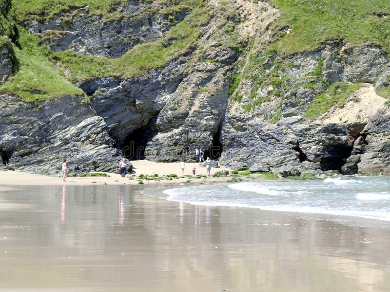 Undersökande grottor på den Portreath stranden. arkivfoto