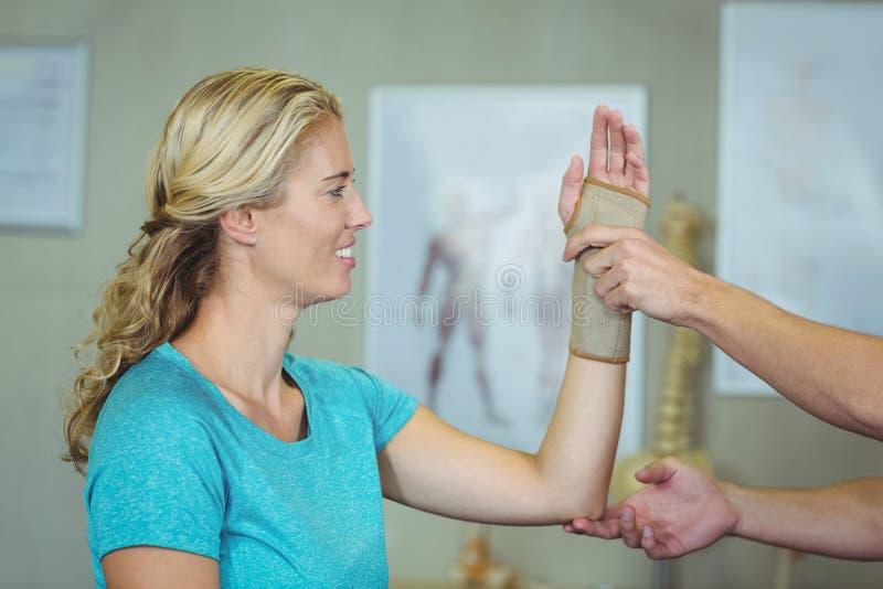 Undersökande hand för manlig fysioterapeut av en kvinnlig patient arkivbilder