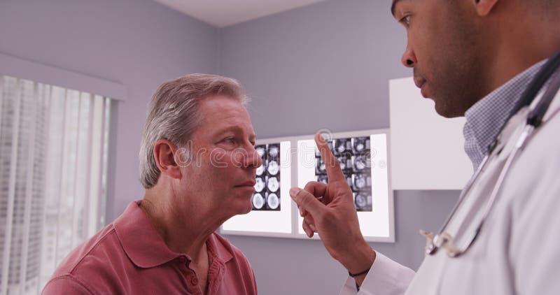 Undersökande head trauma för afrikansk amerikandoktor av hög caucasia royaltyfri fotografi