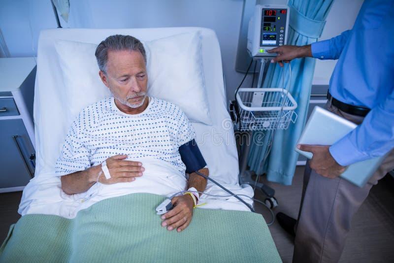 Undersökande hjärtahastighet för doktor av patienten fotografering för bildbyråer